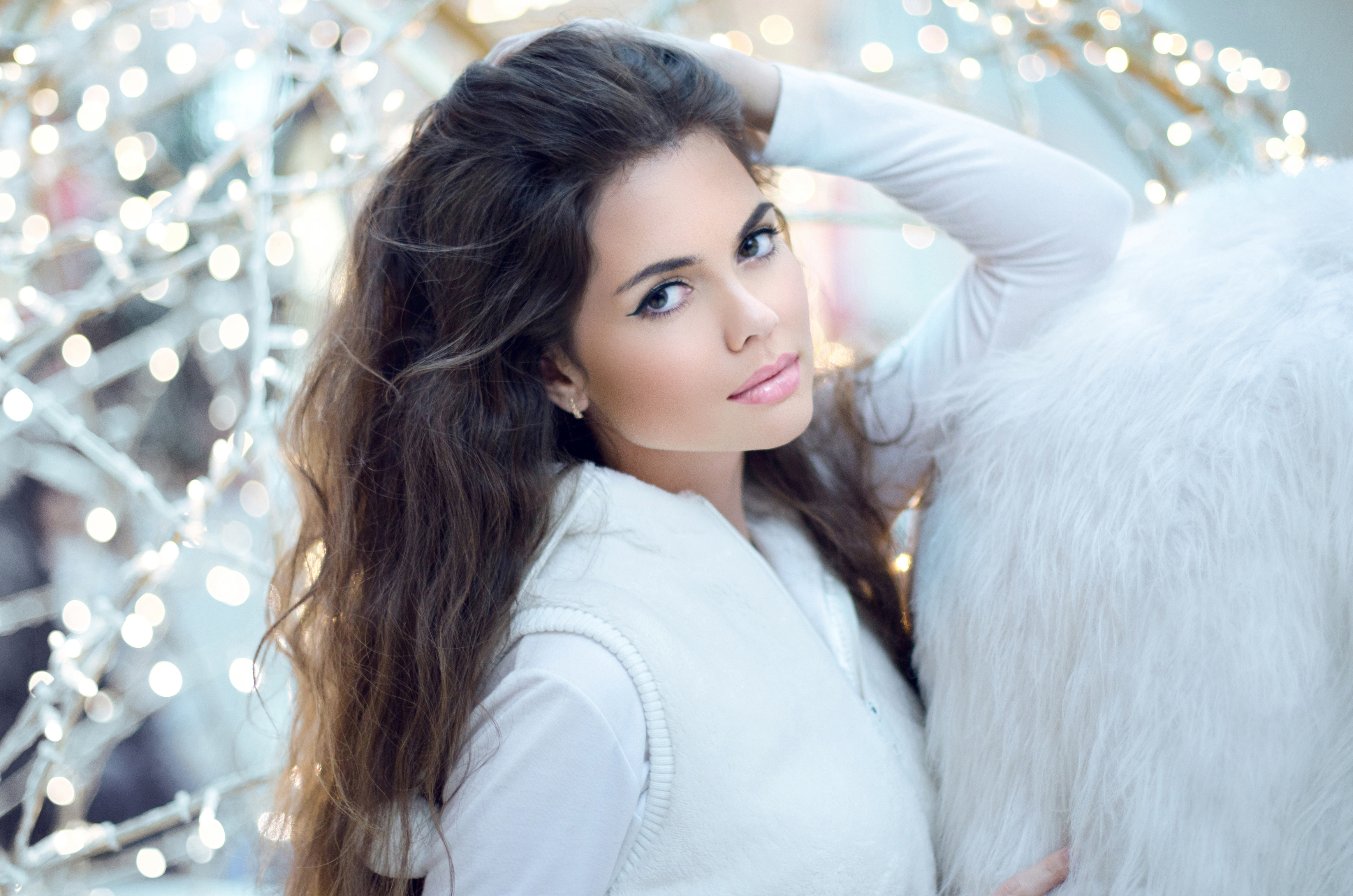 Winter Beauty Woman. Beautiful brunette girl with long hair posing over snow blinking lights background